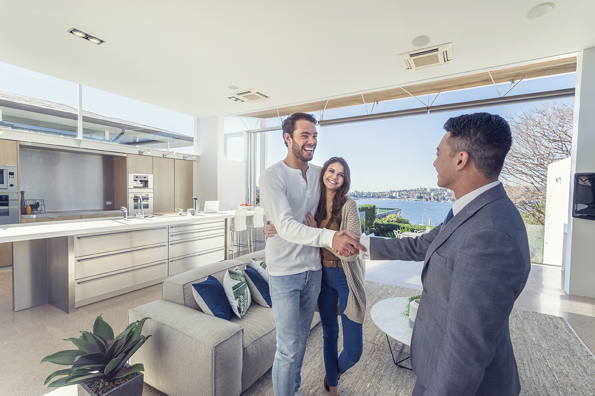 Man and women in new apartment. Man shaking real estate agent's hand.
